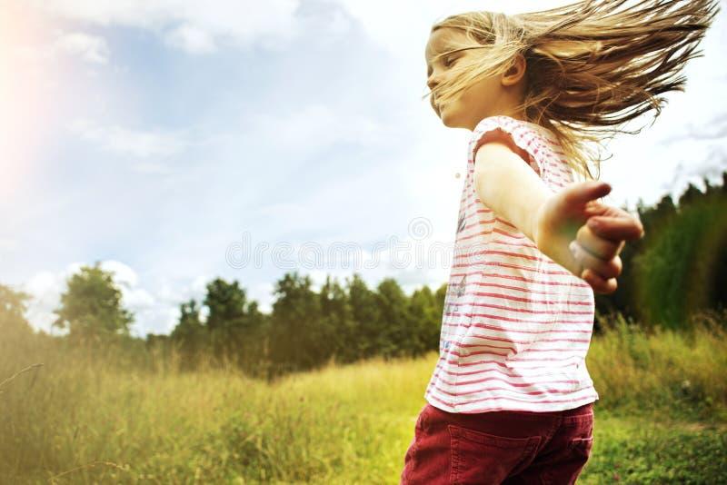 Mała dziewczynka bieg przez pole przy zmierzchem fotografia royalty free