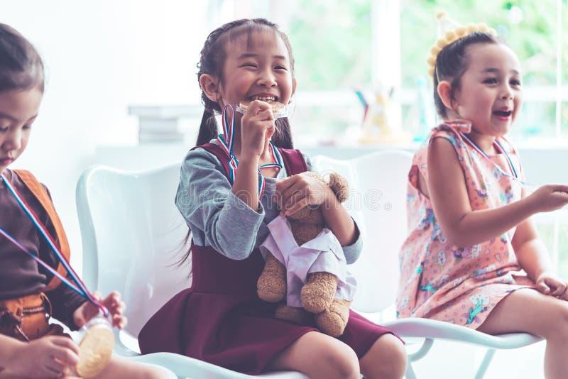 Mała dziewczynka bitting złoty medal dla studenckiej nagrody fotografia stock