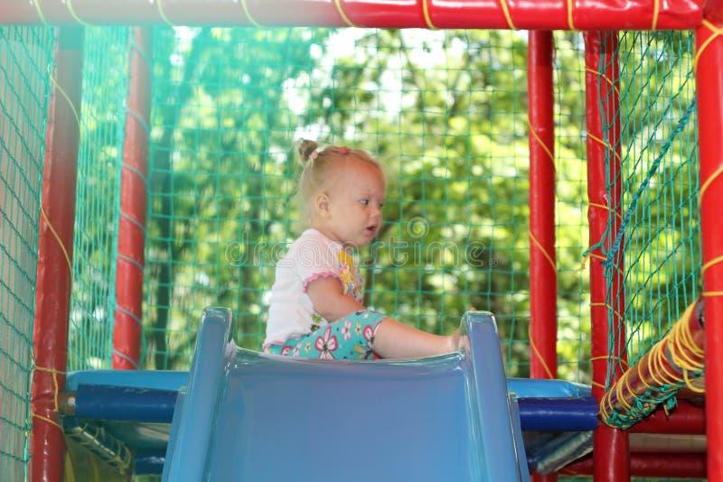 Mała dziewczynka blisko minych obruszeń przy plenerowym rozrywkowym boiskiem zdjęcia royalty free