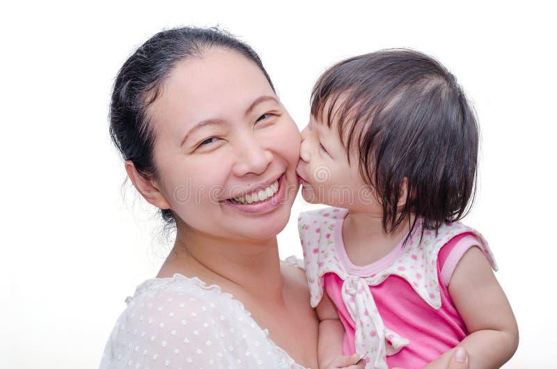Mała dziewczynka całuje jej mamy obraz royalty free