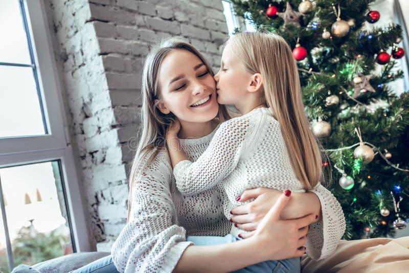 Mała dziewczynka całuje jej mamy na policzku obrazy stock