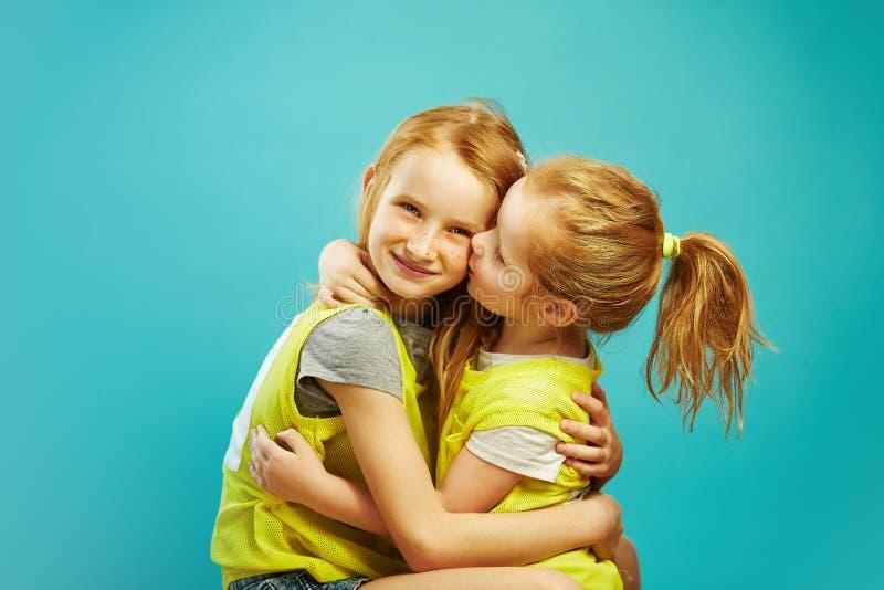 Mała dziewczynka całuje jej starej siostry na błękitnym tle obrazy stock
