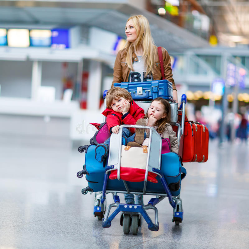 Mała dziewczynka, chłopiec i potomstwo matka z walizkami na lotnisku obraz royalty free