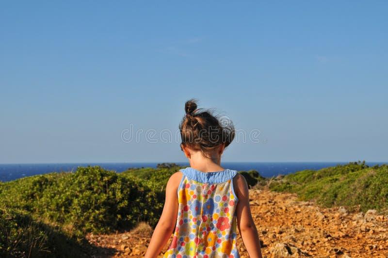 Mała dziewczynka chodzi wybrzeże w kwiecistej sukni obrazy stock