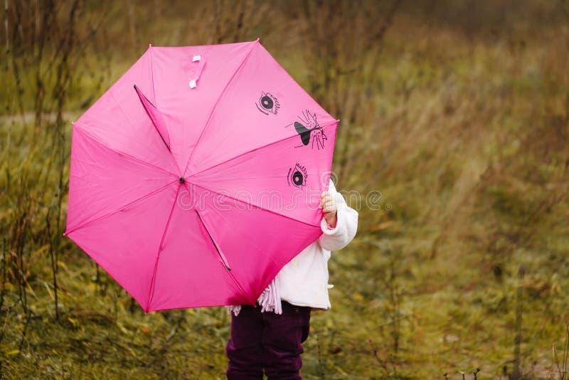 Download Mała Dziewczynka Chowałem Pod Różowym Parasolem W Jesień Parku Obraz Stock - Obraz złożonej z lifestyle, śmiech: 42525927