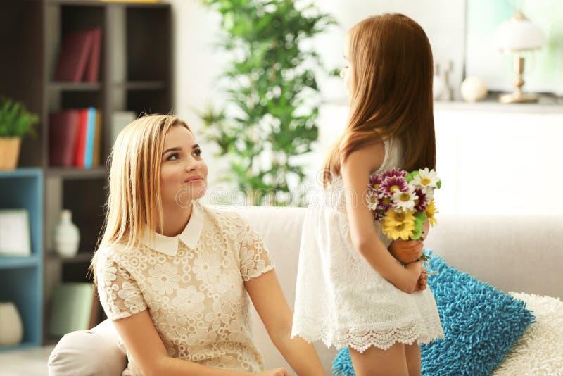 Mała dziewczynka chuje bukiet kwiaty dla jej matki za plecy obraz royalty free