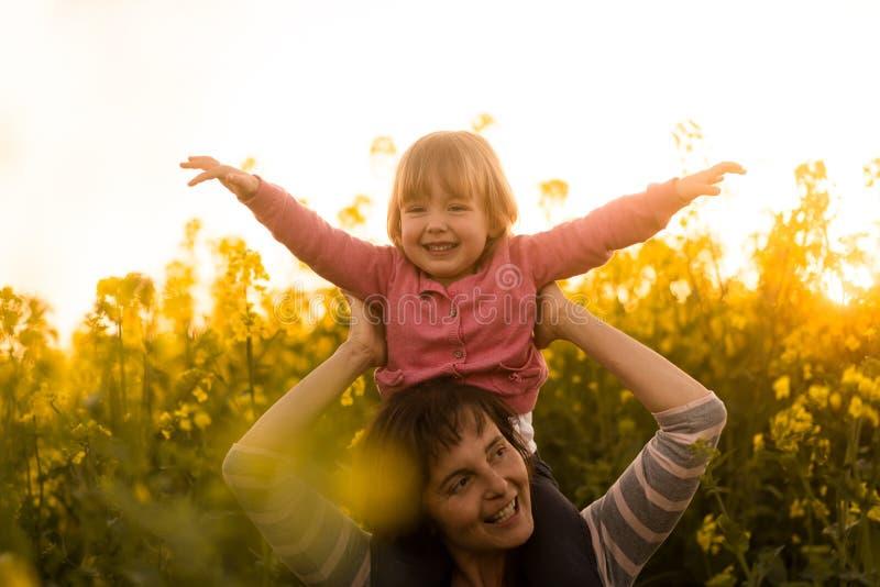 Mała dziewczynka cieszy się przejażdżkę na jej matki ramieniu zdjęcie royalty free