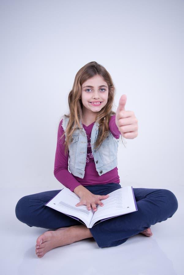 Mała Dziewczynka czyta książkę i robi pozytywnemu znakowi zdjęcia stock