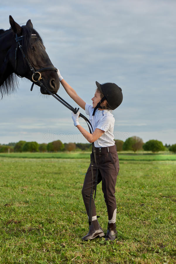Mała dziewczynka dżokej komunikuje z jej czarnym koniem w fachowym stroju zdjęcia stock