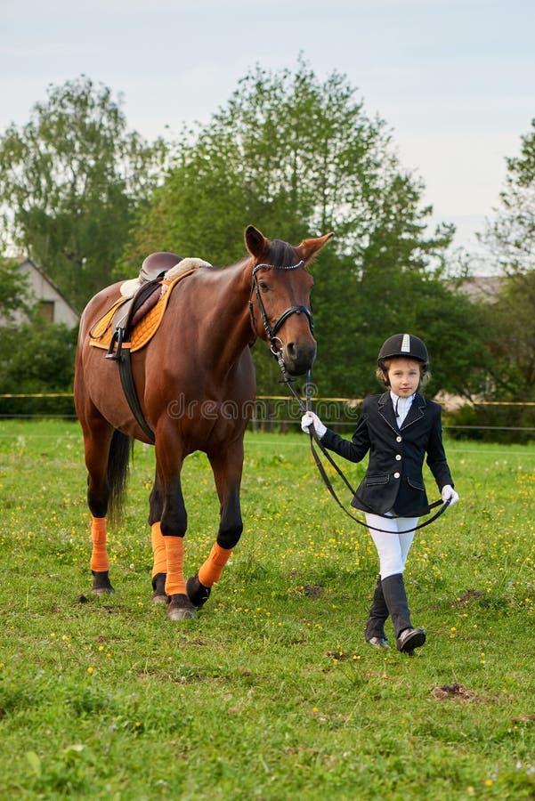 Mała dziewczynka dżokeja prowadzenia koń swój ogranicza przez kraj w fachowym stroju zdjęcia royalty free