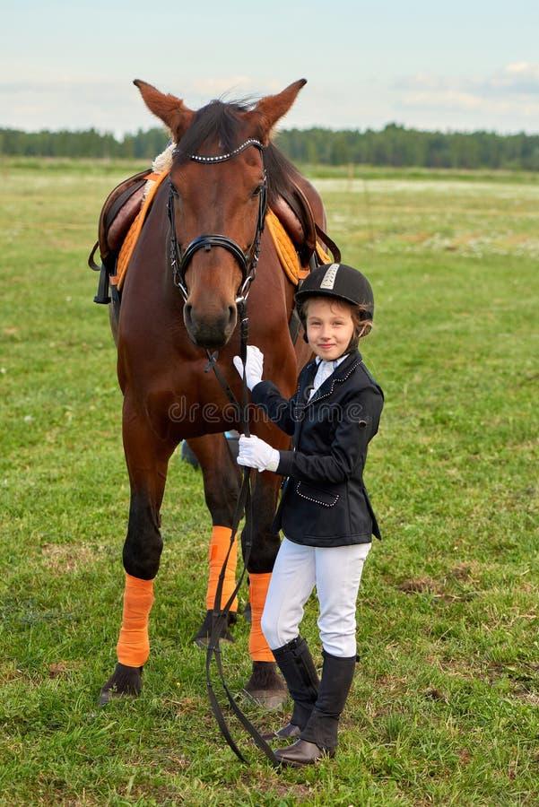 Mała dziewczynka dżokeja prowadzenia koń swój ogranicza przez kraj w fachowym stroju obraz royalty free