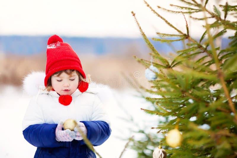 Mała dziewczynka dekoruje boże narodzenia trzy outdoors zdjęcie royalty free