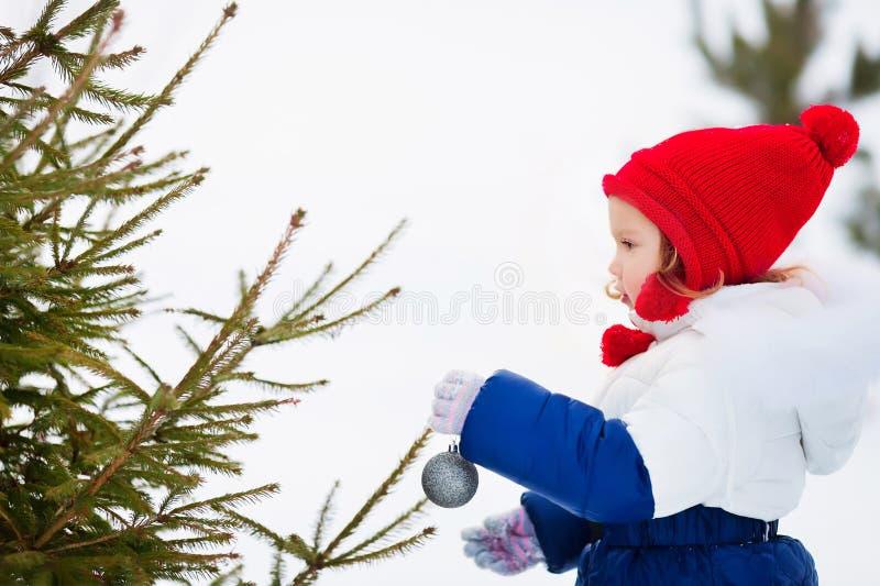 Mała dziewczynka dekoruje boże narodzenia trzy outdoors obrazy royalty free