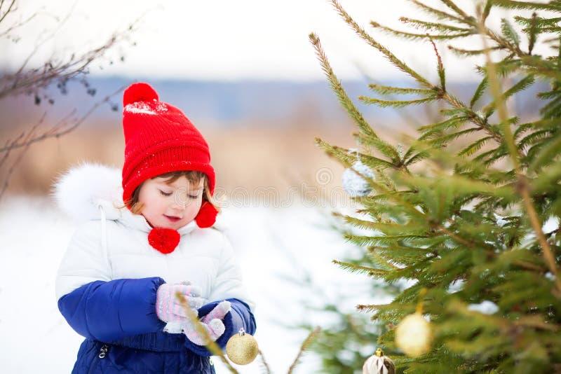 Mała dziewczynka dekoruje boże narodzenia trzy outdoors obrazy stock
