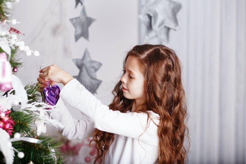 Mała dziewczynka dekoruje choinki z zabawkami i kwiatami fotografia stock