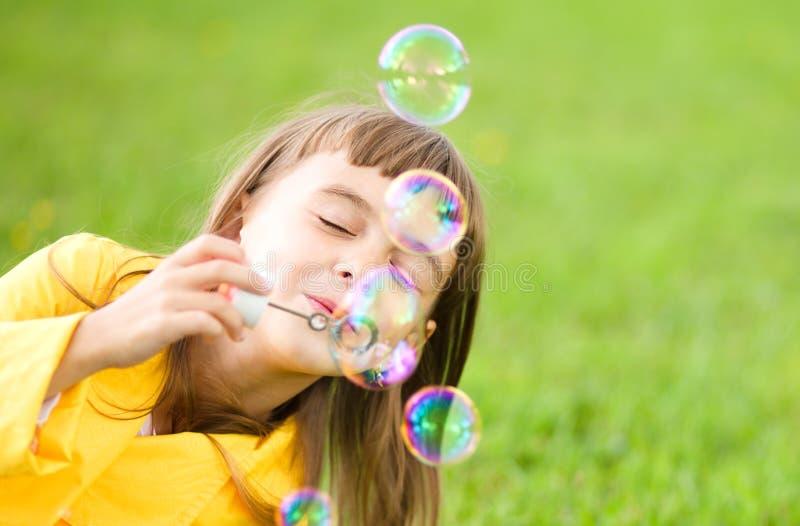 Mała dziewczynka dmucha mydlanych bąble obraz stock