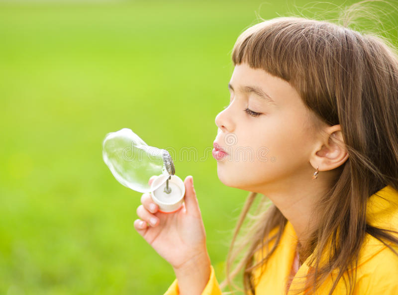 Mała dziewczynka dmucha mydlanych bąble fotografia stock