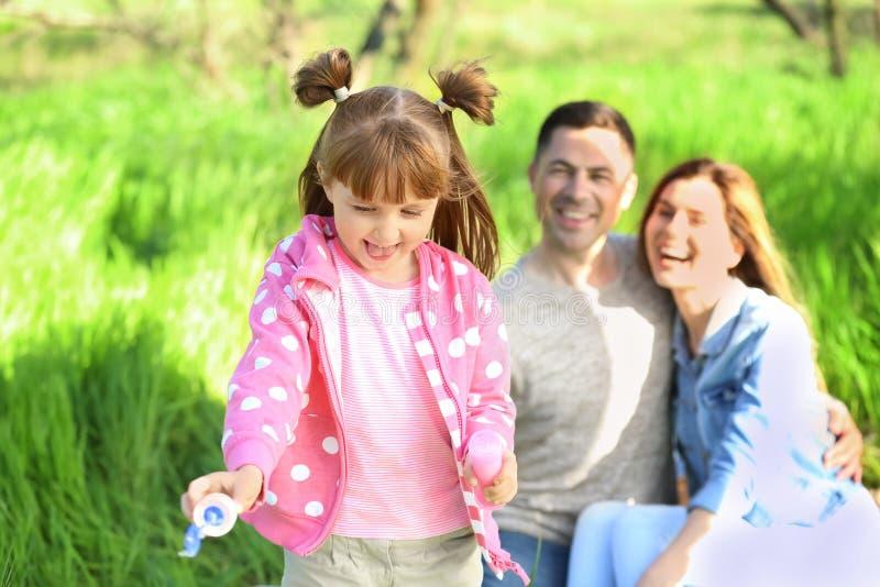Mała dziewczynka dmucha mydlanych bąble podczas gdy odpoczywający w parku z rodzicami zdjęcia royalty free