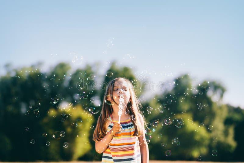 Mała dziewczynka dmucha mydlanych bąble w parku zdjęcia stock