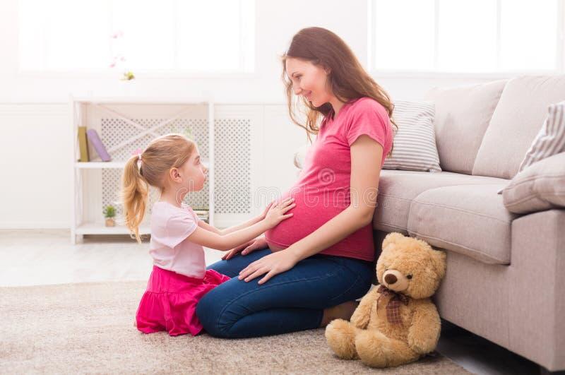 Mała dziewczynka dotyka jej ciężarnego macierzystego brzucha obrazy royalty free