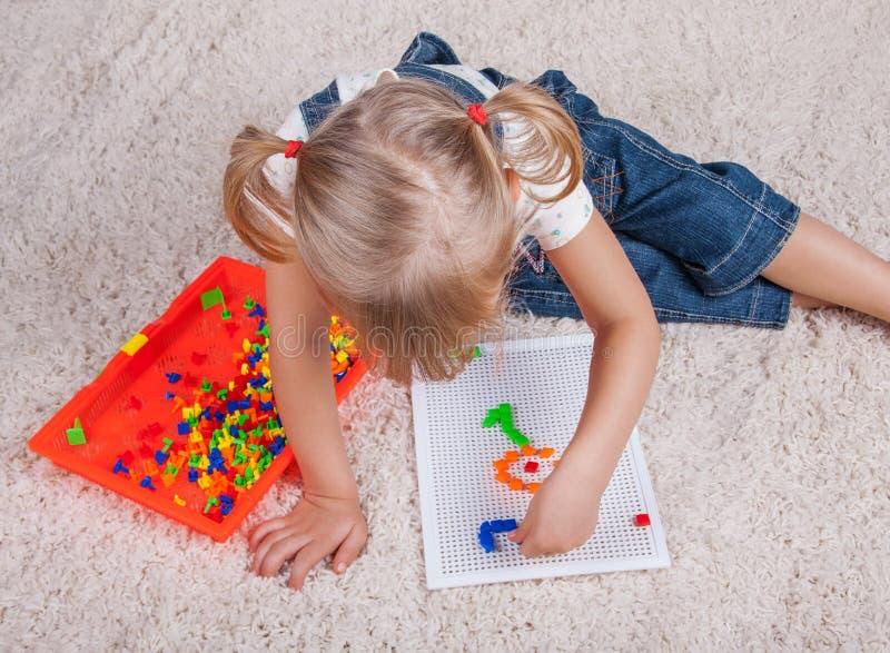 Mała dziewczynka dzieciak bawić się z edukaci mozaiki szpilkami zdjęcie royalty free