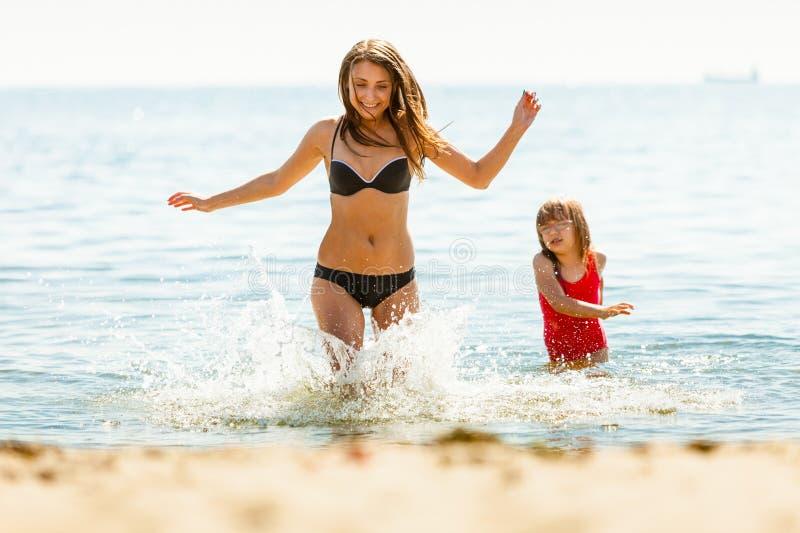 Mała dziewczynka dzieciak i kobiety matka w wodzie morskiej Zabawa zdjęcia stock