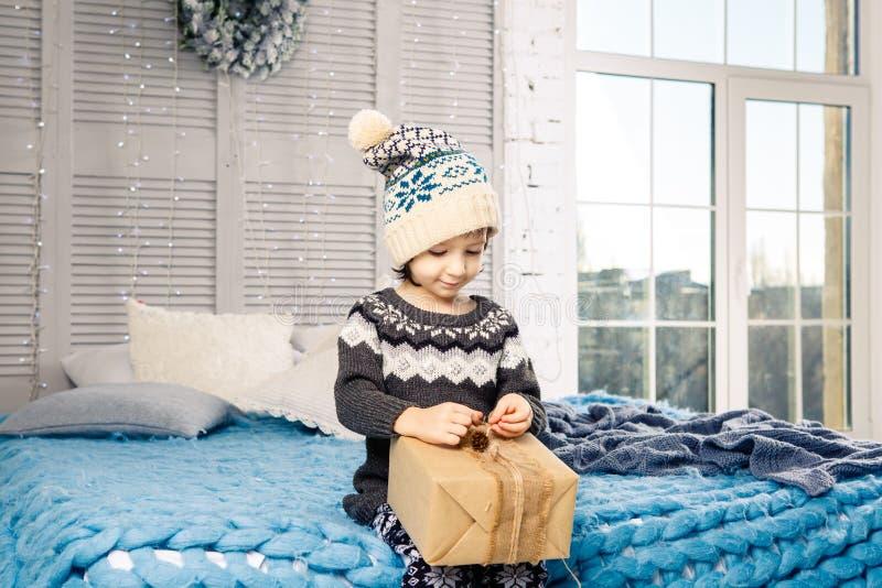 Mała dziewczynka dziecka obsiadanie w piżamach i kapeluszu na łóżku z girlandą żarówki z prezentów pudełkami zawijającymi w barwi zdjęcia royalty free