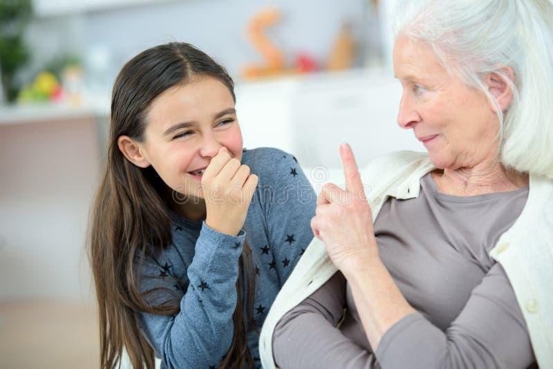 Mała dziewczynka i babcia szepcze sekrety zdjęcia stock