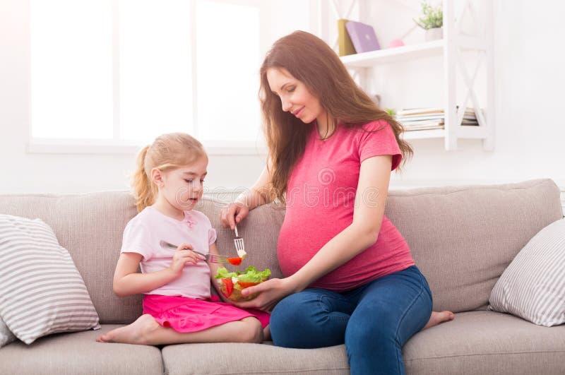 Mała dziewczynka i jej mamy łasowania sałatka w domu fotografia stock