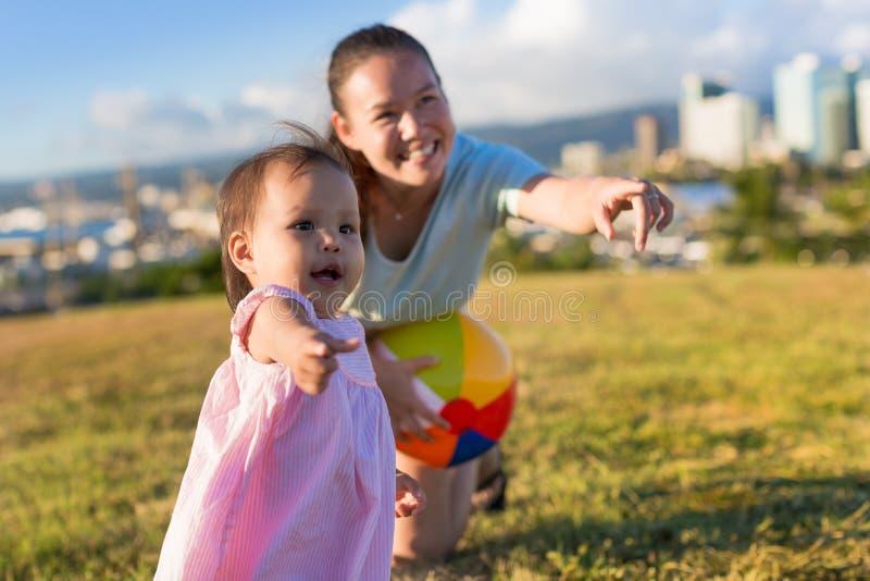 Mała dziewczynka i jej matka learing bawić się balowe gry w ładnym popołudniu przy parkiem fotografia stock