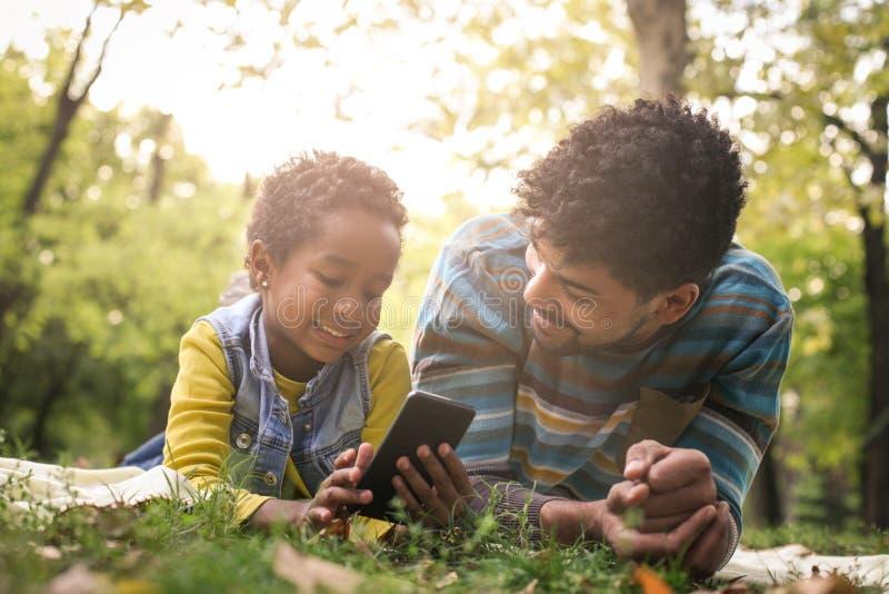 Mała dziewczynka i jej ojca łgarski puszek wewnątrz parkujemy a zdjęcia royalty free