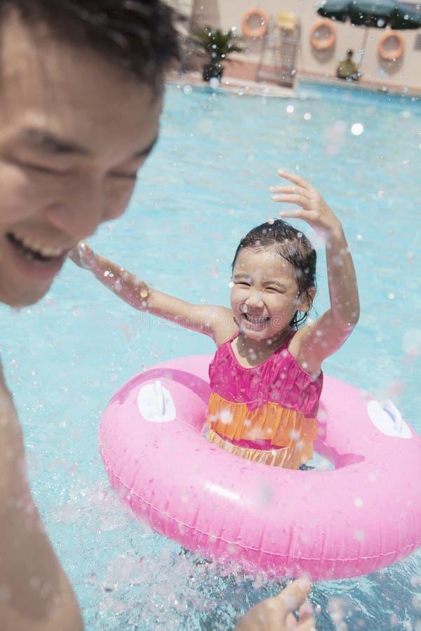Mała dziewczynka i jej ojca chełbotanie w basenie zdjęcie royalty free