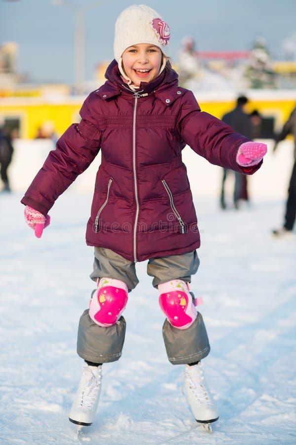 mała dziewczynka jeździć na łyżwach przy lodowiskiem w kolanowych ochraniaczach zdjęcia stock