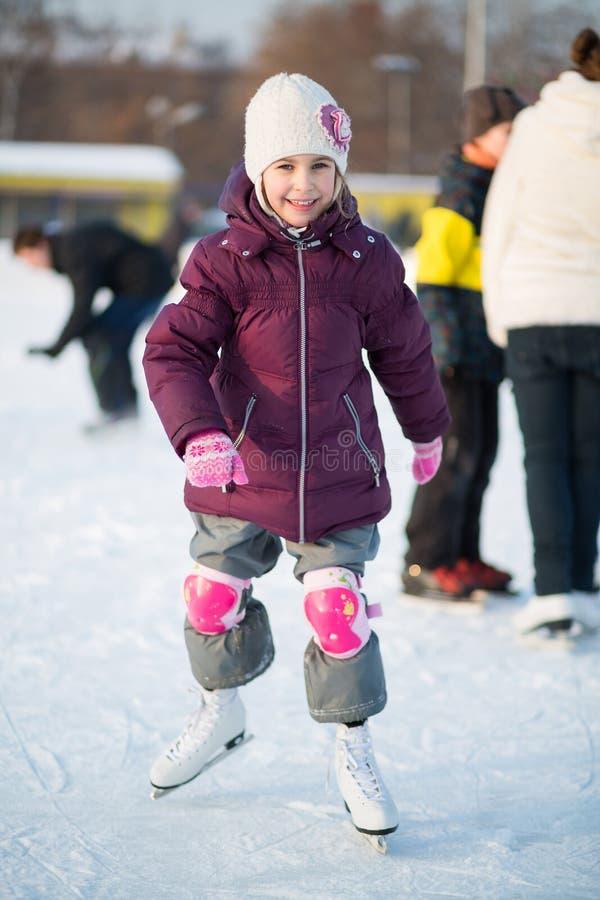 Mała dziewczynka jeździć na łyżwach przy lodowiskiem w kolanowych ochraniaczach fotografia royalty free