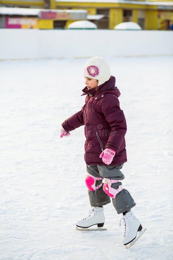 Mała dziewczynka jeździć na łyżwach przy lodowiskiem w kolanowych ochraniaczach fotografia stock