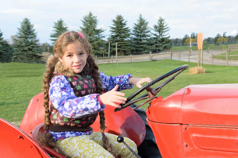 Mała dziewczynka jeździecki ciągnik zdjęcie royalty free