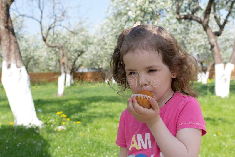 Mała dziewczynka je tort przy pinkinem obrazy royalty free
