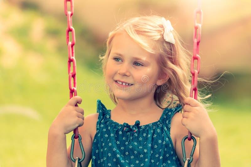 Mała dziewczynka jedzie na huśtawce zdjęcia royalty free