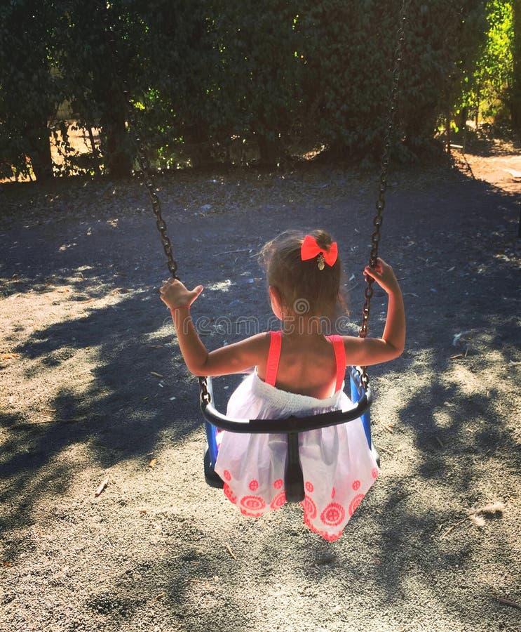 Mała dziewczynka jedzie na huśtawce obrazy royalty free
