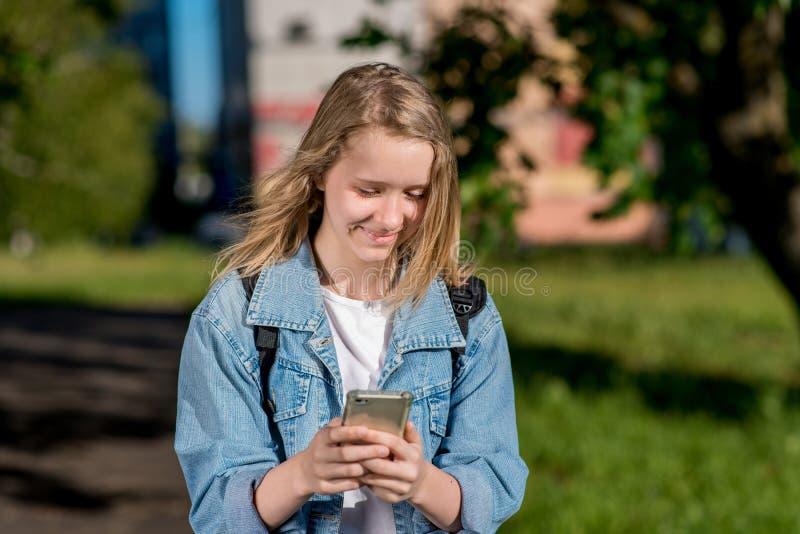 Mała dziewczynka jest blondynką Uczennica w lecie po szkoły W jego rękach trzyma smartphone Uśmiechy szczęśliwie pisze zdjęcia stock