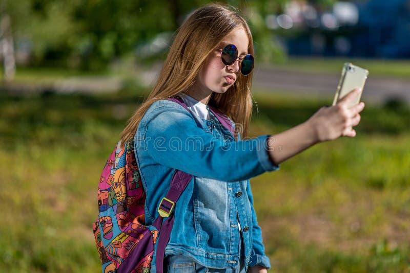 Mała dziewczynka jest blondynką W lato parka świeżym powietrzu Za plecy jest piękny plecak W rękach trzyma smartphone obraz stock