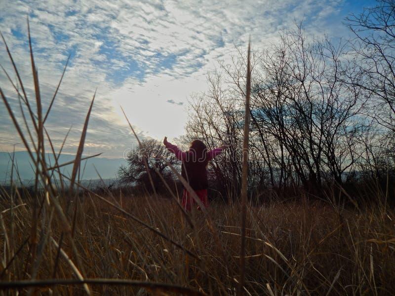 Mała dziewczynka jest przyglądająca dostawać z słońca w naturze naprzód zdjęcia royalty free