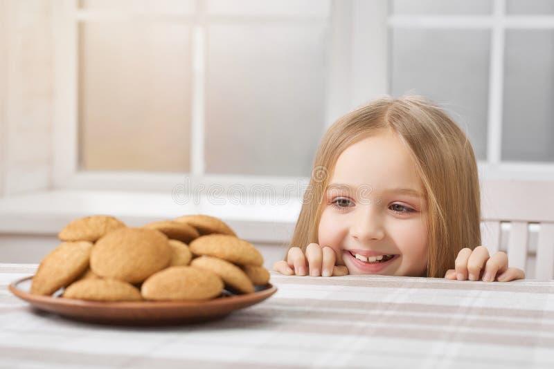Mała dziewczynka jest przyglądająca na wyśmienicie ciastkach i uśmiechach fotografia stock