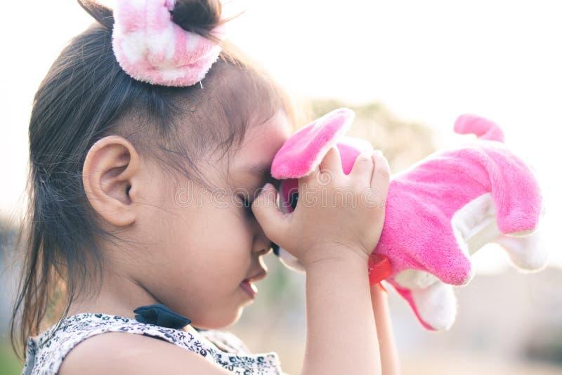 Mała dziewczynka jest szczęśliwa bawić się psią lalę w ogródzie fotografia stock