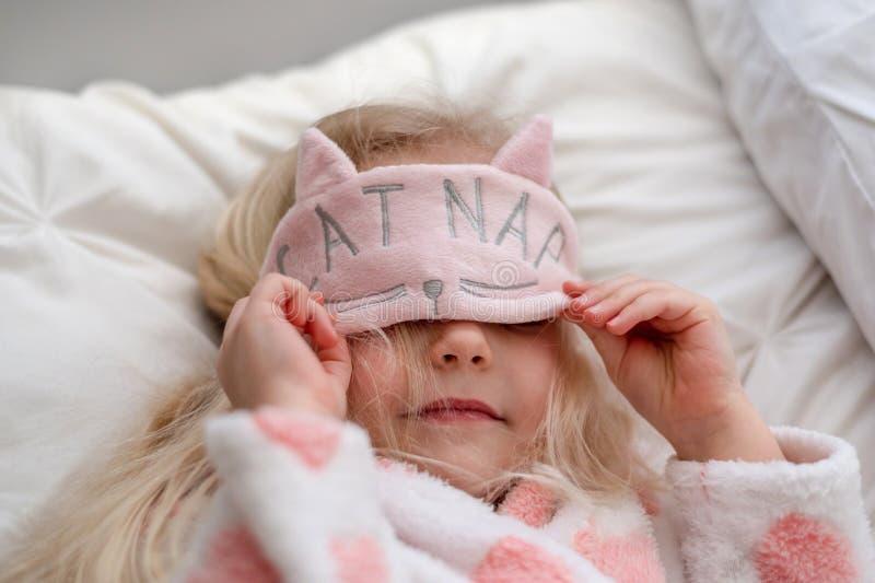 Mała dziewczynka jest ubranym kot drzemki maskę fotografia stock