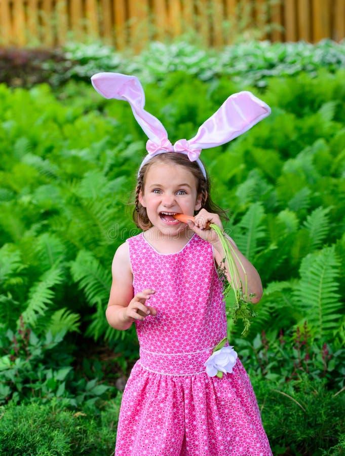 Mała Dziewczynka Jest ubranym królików ucho Je marchewki zdjęcie royalty free