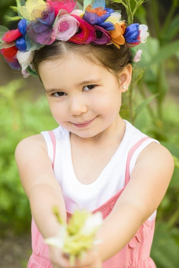 Mała dziewczynka jest ubranym kwiatu wianek i bukiet kwiat zdjęcia stock