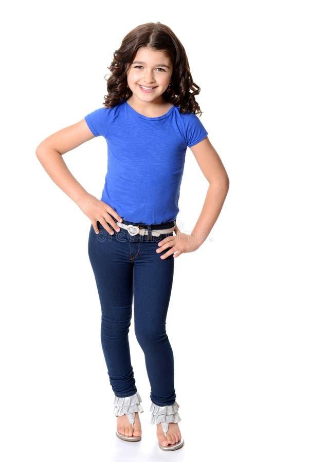 Mała dziewczynka jest ubranym niebieskich dżinsy z rękami na biodrach obraz stock