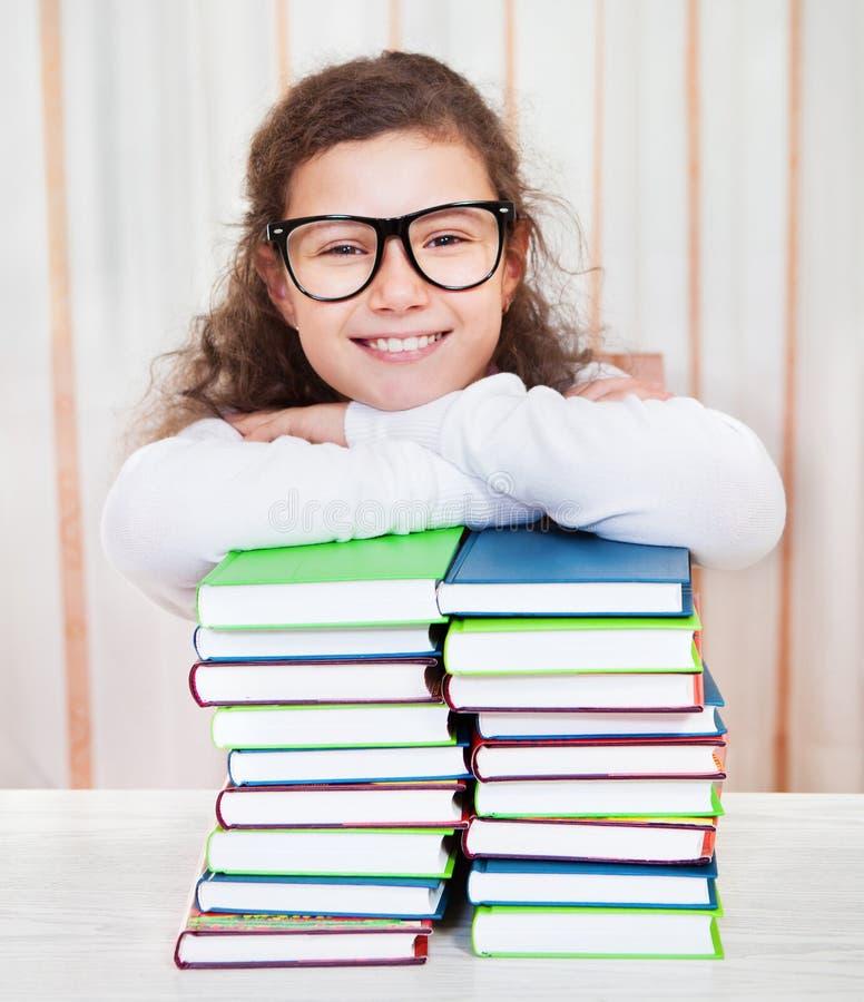 Mała dziewczynka jest ubranym szkła z stosem książki obrazy royalty free