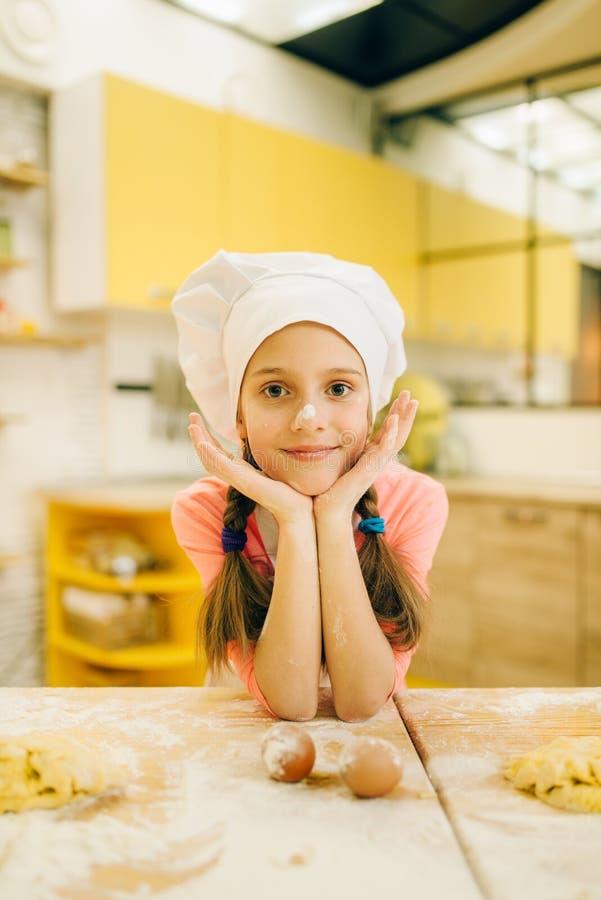 Mała dziewczynka kucharz w nakrętce i fartuchu na kuchni fotografia stock